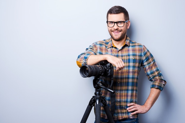 Professional photographer. portrait of confident young man in shirt holding hand on camera on tripod while standing against grey background