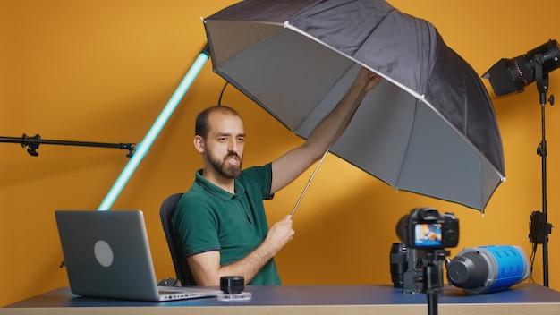 スタジオで傘のレビューを記録するプロの写真家。仕事、写真スタジオのソーシャルメディアスターおよびインフルエンサーのためのプロのスタジオビデオおよび写真機器技術