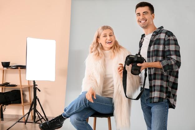 Профессиональный фотограф показывает фотографии модели в студии