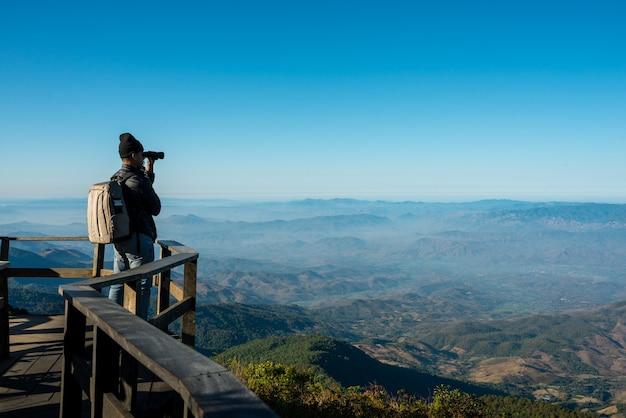 Профессиональный фотограф делает пейзажные фотографии камерой на горе, путешествии, рюкзаке
