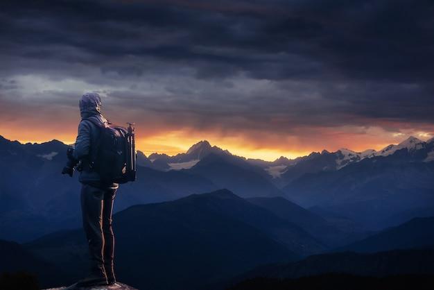 Профессиональный фотограф делает фотографии с большой камерой на вершине скалы