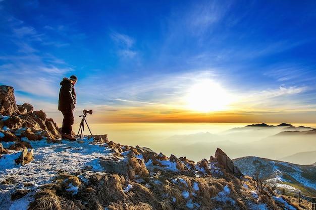 전문 사진 작가가 일몰 바위 봉우리에 삼각대에 카메라로 사진을 찍습니다.