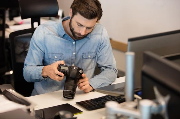 Профессиональный фотограф с помощью камеры в творческом офисе
