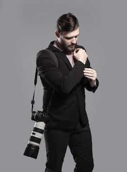 커프스 단추를 조정하는 카메라가있는 전문 사진 작가