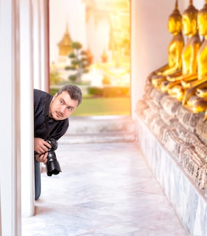 Professional photographer with digital camera in buddha temple