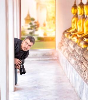 仏寺院でデジタルカメラを持つプロの写真家