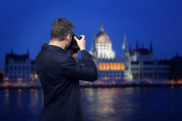 Professional photographer with  digital photo camera takes night pictures of palace on the river