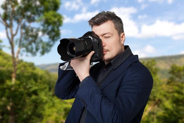 デジタル写真カメラを持つプロの写真家が写真を撮る、緑の自然