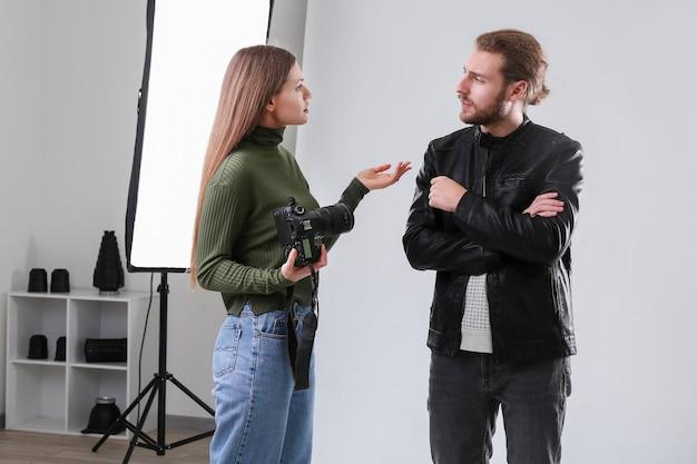 Профессиональный фотограф с моделью в студии