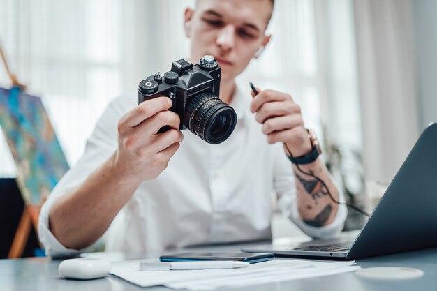 入れ墨の腕を持つプロの写真家は、彼がそれを保持しているフォトカメラを見ます。オフィスで働くフォーマルな服を着ている流行に敏感な男。