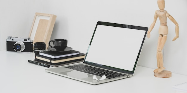 Professional photographer workplace with open blank screen laptop, camera and office supplies