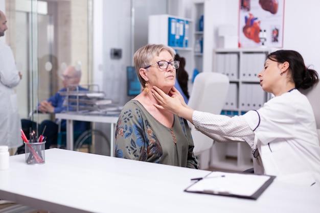 老婆の首のリンパ節をチェックし、年配の女性を触診する専門医。病院の高齢患者訪問医が診療所で甲状腺の喉に触れて健康を調べ、治療医療