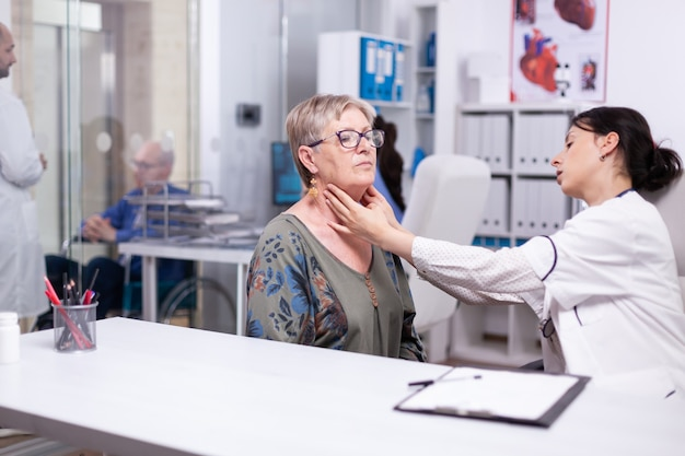 Professional physician checking neck lymph nodes of old woman, palpating senior woman. elderly patient visiting doctor at hospital examining thyroid throat touching health at clinic, treatment medical