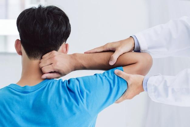 Профессиональные физиотерапевты оказывают помощь пациентам-мужчинам с травмами руки, осматривают пациентов в клинике проведение реабилитационной терапии боли в клинике концепция реабилитационной физиотерапии
