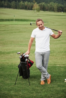 A professional player stands on a golf course, holds a metal bag and a golf bag