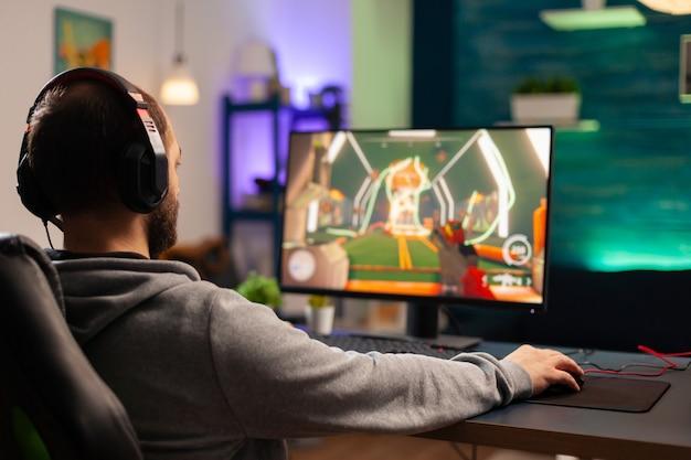Профессиональный игрок с гарнитурой, играющий в видеоигры с современной графикой для соревнований шутеров. онлайн-трансляция кибер-выступления во время игрового турнира с использованием технологии беспроводной сети