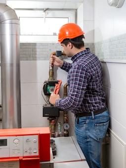 Professional plumber in hard hat repairing heating system
