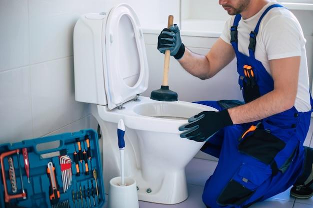 制服を着たプロの配管工が道具の助けを借りて家庭用バスルームの便器を修理しています