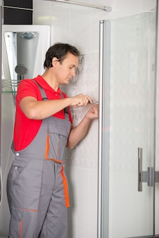 Professional plumber is repairing a shower.