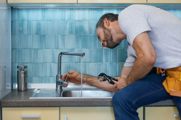Профессиональный сантехник сосредоточенно использует трубный ключ, осматривая и фиксируя кран в