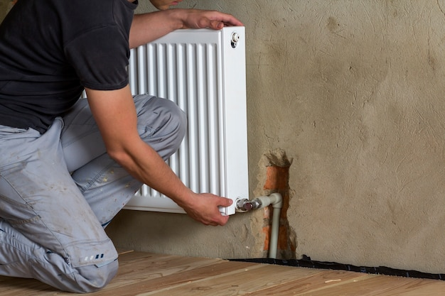 Professional plumber worker installing heating radiator on brick wall in an empty room of a newly built apartment or house. construction, maintenance and repair concept.