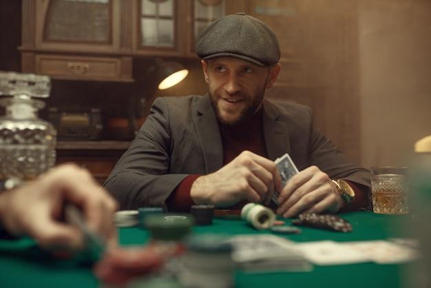 プロのポーカープレーヤーはリスクを感じています。運が左右するゲーム。ギャンブルの家でのレジャーの手にカードを持つ男
