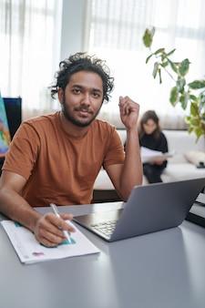 男性デザイナーのプロの肖像画と、オフィスのテーブルに座っている巻き毛とラップトップの仕立て屋。あごひげを生やしたうれしそうなインド人労働者。