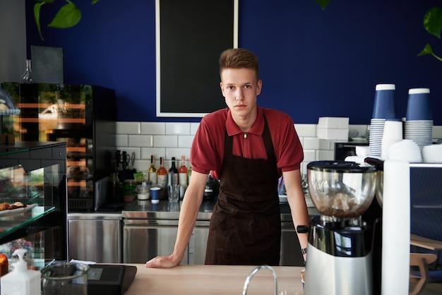 コーヒーショップのバーカウンターの後ろに若い訓練されたバリスタのプロの肖像画。中小企業、飲食物ビジネスの概念