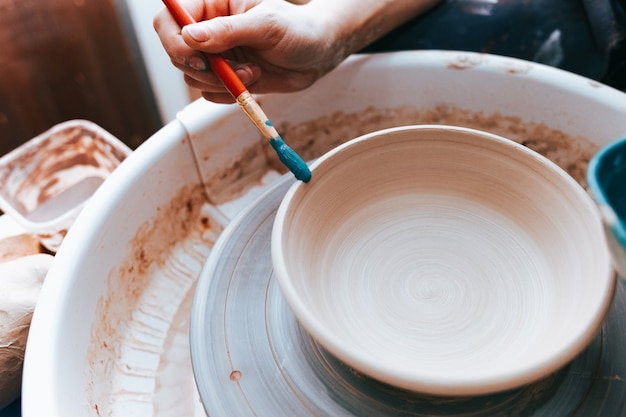 Professional potter works on painting plates in the workshop.