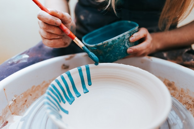 Professional potter works on painting plates in the workshop