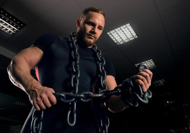 Профессиональный пауэрлифтер стоит в тренажерном зале с железными цепями, обмотанными вокруг его рук
