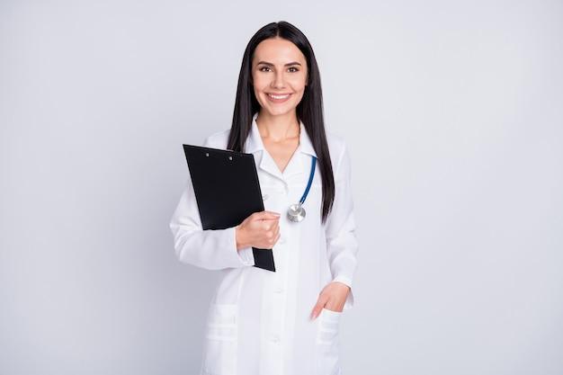 Профессиональный практикующий леди в белом лабораторном халате держит буфер обмена на сером фоне