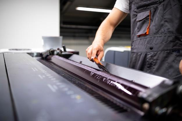 인쇄소에서 인쇄하는 동안 더 많은 색상을 추가하는 전문 인쇄 기계 운영자.