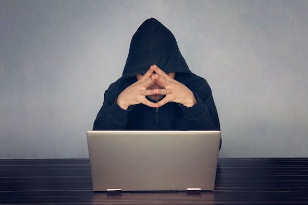 Professional programmer thinking how to design developing online steal system through code language and hacking identity information, thoughtful hacker in a black hood, picks up the password.