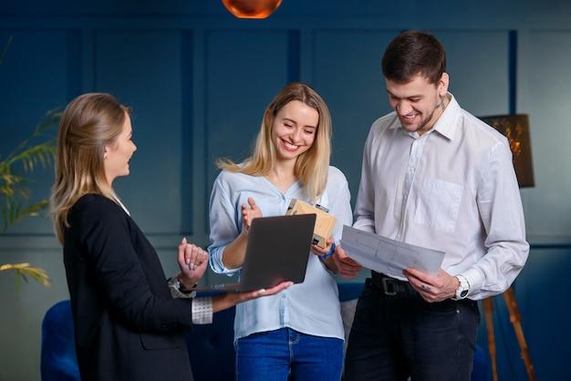 プロの不動産業者、デザイナーがラップトップで将来のデザインの計画をカップルのクライアントに見せます。