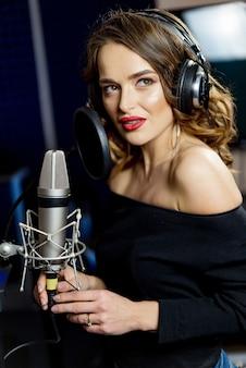 スタジオでの曲のプロのレコード。マイクの近くのヘッドフォンで美しい女性。レコーディングスタジオの暗い背景の女の子。肖像画。閉じる。