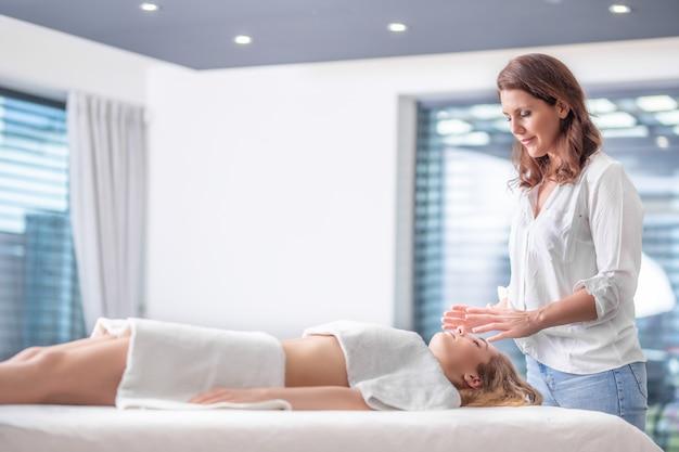그녀의 손을 통해 에너지를 보내는 매력적인 여성 클라이언트의 머리 위에 서 있는 전문 레이키 치료사.