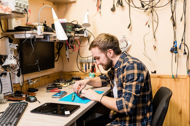 Professional repairman bending over demounted smartphone and fixing tiny details with help of tweezers in workshop