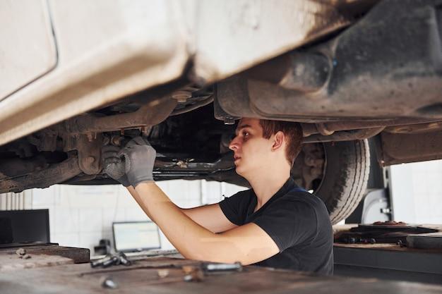 Professional repairman in black shirt works under broken automobile