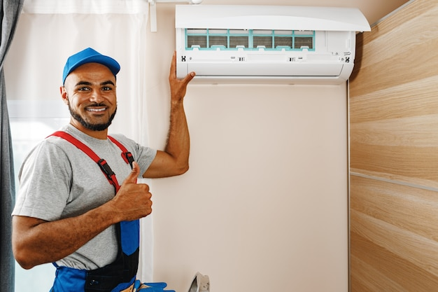 Professional repairman installing air conditioner in a room close up