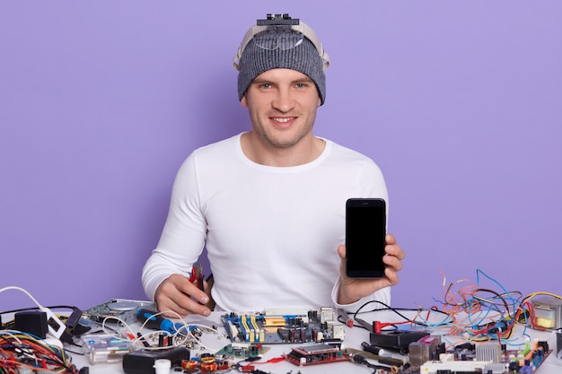 Professional repairman repairing broken smart phone, showing blank screen with copy space for advertisment