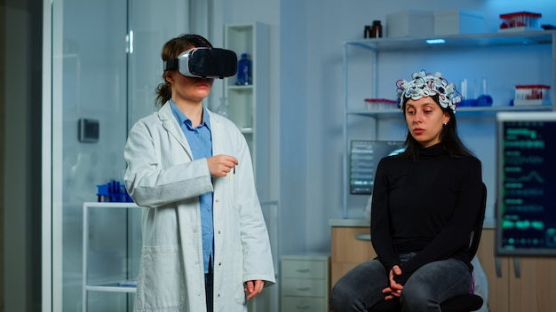 患者の脳スキャンを分析する研究室で医療イノベーションを使用してバーチャルリアリティメガネを着用している専門の研究者。機器のハイテクシミュレーターデバイスを使用する神経内科医のチーム