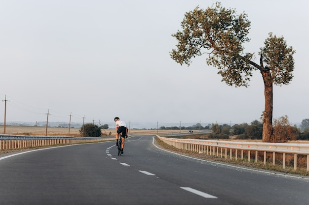 Профессиональный велосипедист в защитном шлеме и спортивной одежде, участвуя в гонках на свежем воздухе