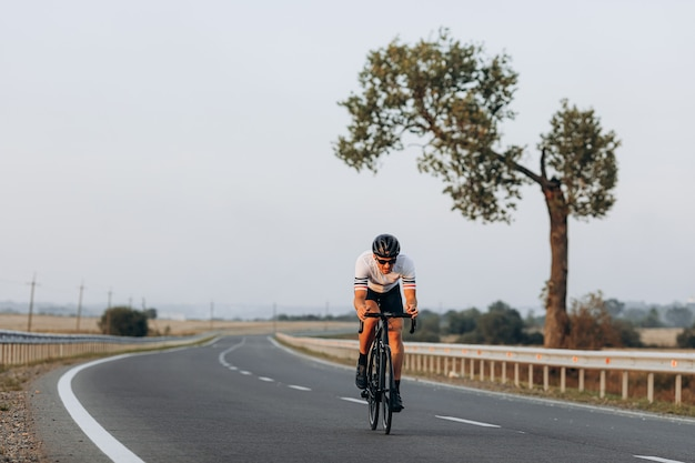 Профессиональный шоссейный велосипедист в защитном шлеме и зеркальных очках, участвуя в гонках на открытом воздухе