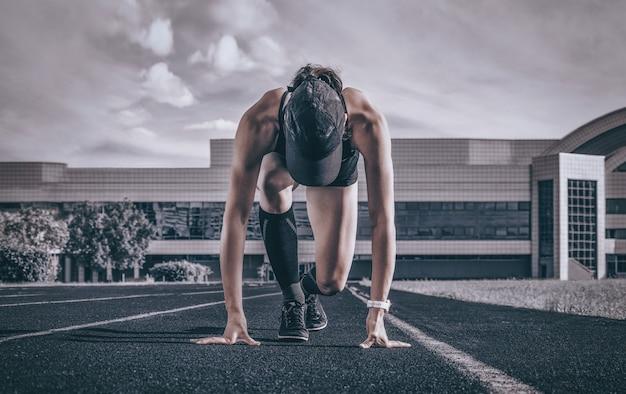 Профессиональный бегун стоит на трассе и готовится к старту. спортивная концепция.
