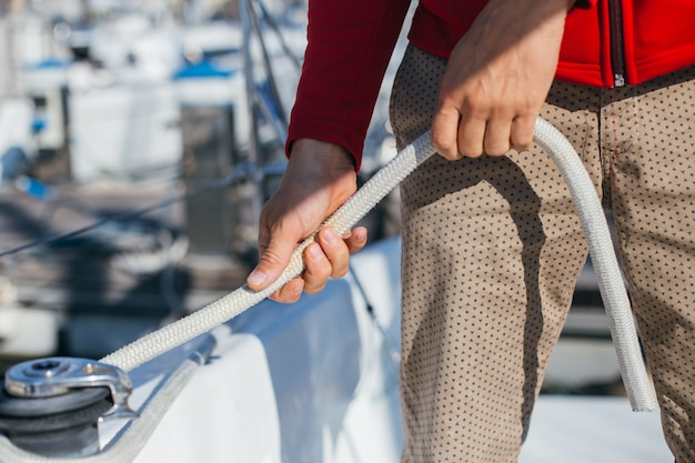 Professional sailor or yachtsman tights and tensions cable or wire rope on mechanical winch on sailboat or yacht