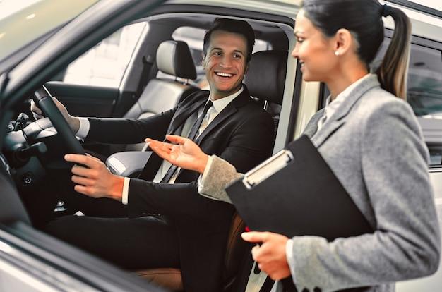自動車販売店で顧客と仕事をしている間の専門の販売員。スーツで成功した青年実業家は新しい車を選びます。