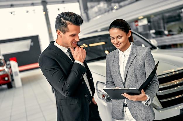 자동차 대리점에서 고객과 일하는 동안 전문 판매원. 양복을 입은 성공적인 젊은 사업가가 새 차를 선택합니다.
