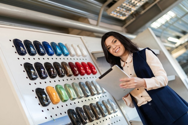 Professional salesperson help to chose color for a car in dealership center