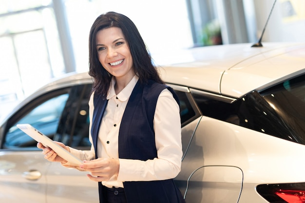 Professional salesperson present a new car in dealership center
